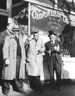 4 men standing outside Cloverleaf historical black and white